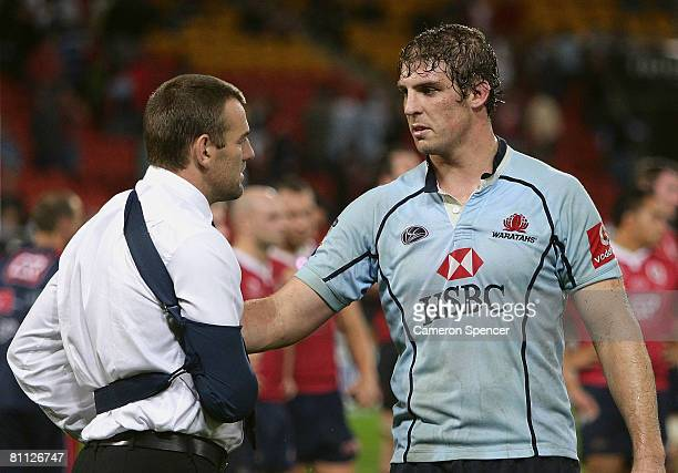 Injured Reds player Chris Latham talks to Dan Vickerman of the Waratahs following the round 14 Super 14 match between the Queensland Reds and the New...