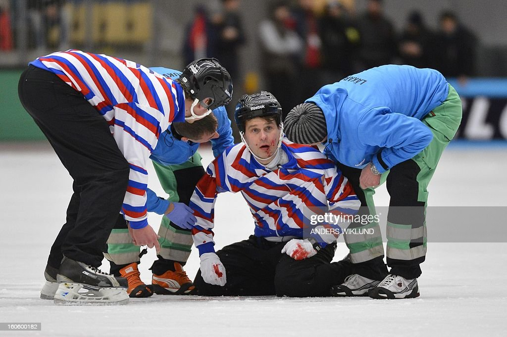 Injured referee Petri Kuusela is helped off the ice after colliding with Sweden's Daniel Mossberg (not in picture) during the Bandy World Championship final match Sweden vs Russia in Vanersborg, Sweden, February 3, 2013.