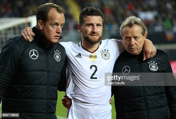 Injured Shkodran Mustafi of Germany leaves the pitch between Doctor Jochen Hahne and physio Klaus Eder during the FIFA 2018 World Cup Qualifier...