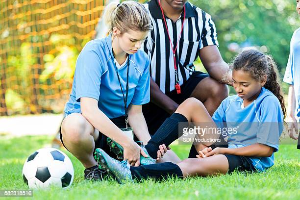 Injured soccer player getting her ankle checked by her coach