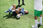 injured soccer player lying on football field during match