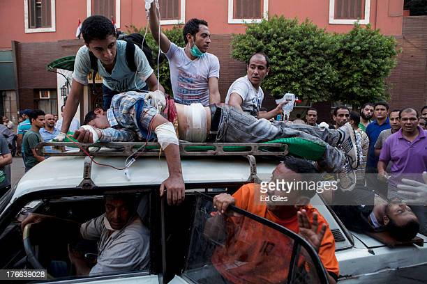 Injured supporters of deposed Egyptian President Mohammed Morsi are driven into the alSednawi hospital near Ramses Square on August 16 2013 in Cairo...