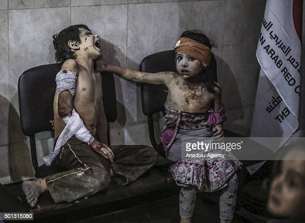 Injured Syrian kids are seen at a field hospital after Assad regime forces' airstrikes on a market in the opposition controlled Damascus suburb of...