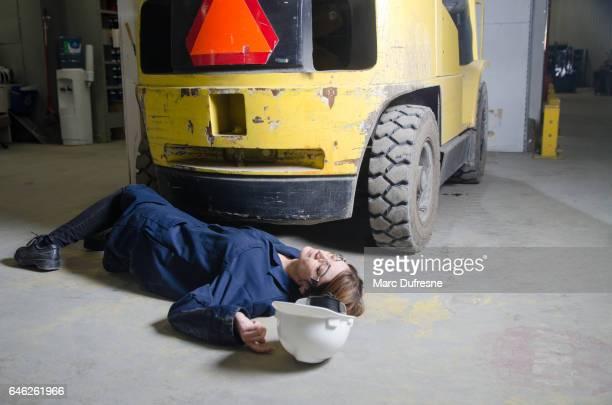 Travailleur de la femme blessée sur le sol devant le véhicule