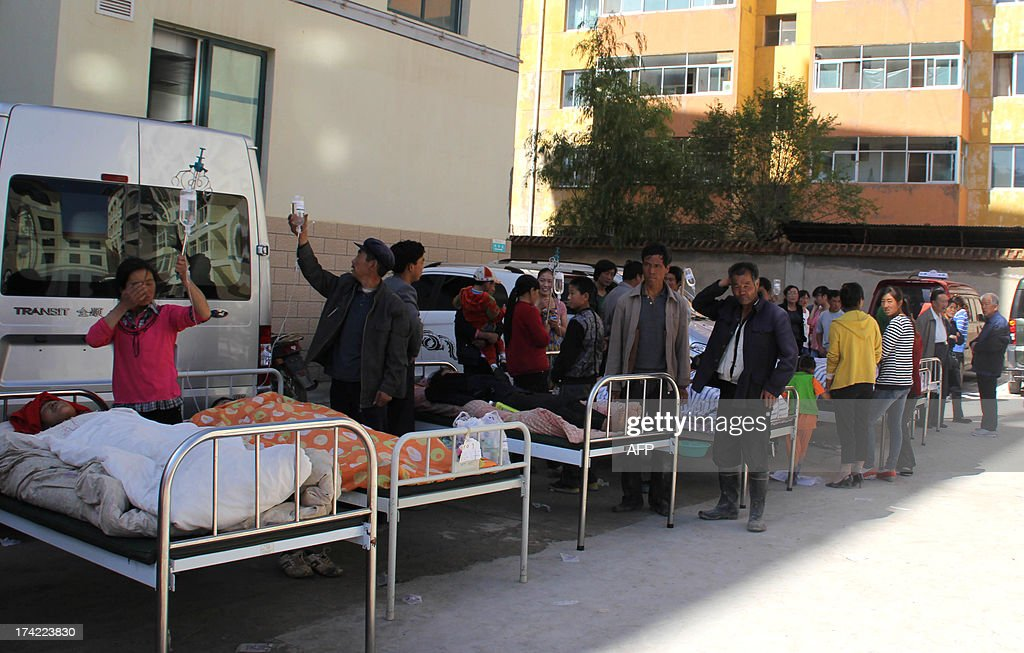 Injuried people lie on beds outside a hospital in Minxian after an eathquake hit the area in Minxian county of Dingxi, northwest China's Gansu province on July 22, 2013. At least 54 people were killed and more than 300 severely injured when two shallow earthquakes struck northwest China early Monday, officials said, as rescuers battled to reach survivors in the remote, mountainous area. CHINA