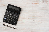 Ink pen and black calculator isolated on wooden texture background
