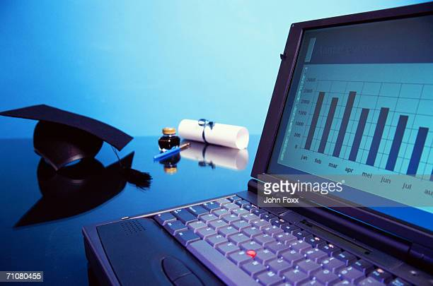 Ink well, fountain pen, graduation certificate by laptop displaying bar graph