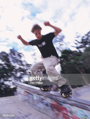 In-line skater performing stunt on railing : Stock Photo