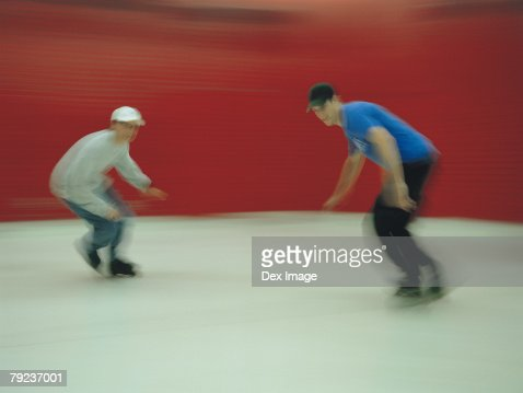 In-line skaters performing stunt in skating ring (blurred motion) : Stock Photo