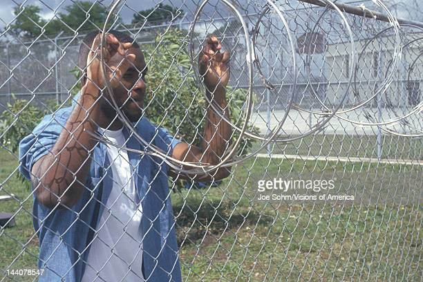 Inmate at barbed wire fence Dade County Men's Correctional Facility Florida