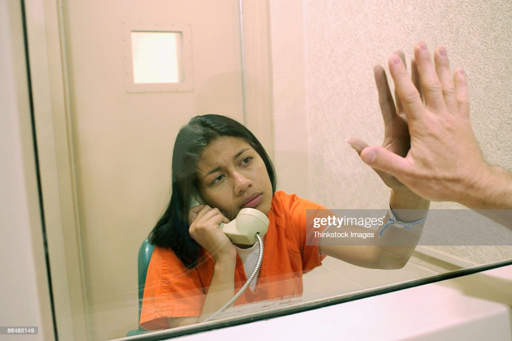 Inmate pressing hand against glass with visitor