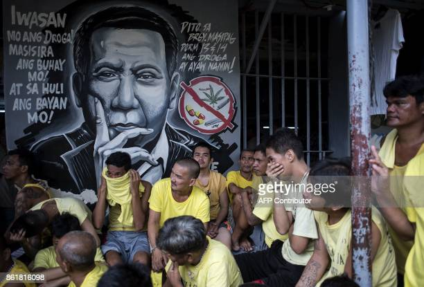 TOPSHOT Inmates are seen beside a wall depicting Philippine President Rodrigo Duterte as authorities search for contraband at the Manila City Jail on...