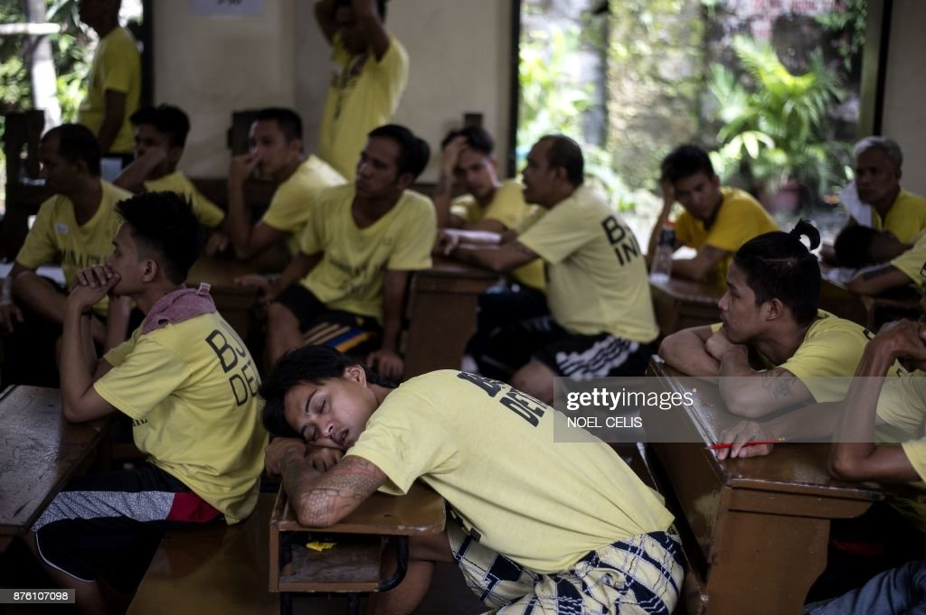 Inmates at the Manila City Jail wait for lunch inside the jail chapel after participating in the National Accreditation and Equivalency Examinationthe alternative learning system in Manila on November 19, 2017. Some 900 inmates, mostly drug related cases, participated in the elementary and highschool exams in the drive to be educated.