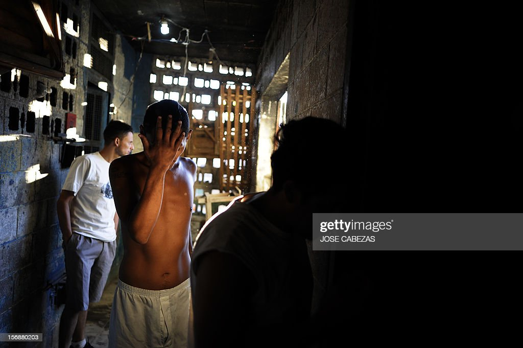 Inmates cover their faces as they walk to their cells to get some belongings after the morning counting at La Esperaza Jail in San Salvador, on November 23, 2012. La Esperanza, the largest jail in El Salvador, was designed to hold 800 inmates but currently holds 4700 prisoners. AFP PHOTO/Jose CABEZAS