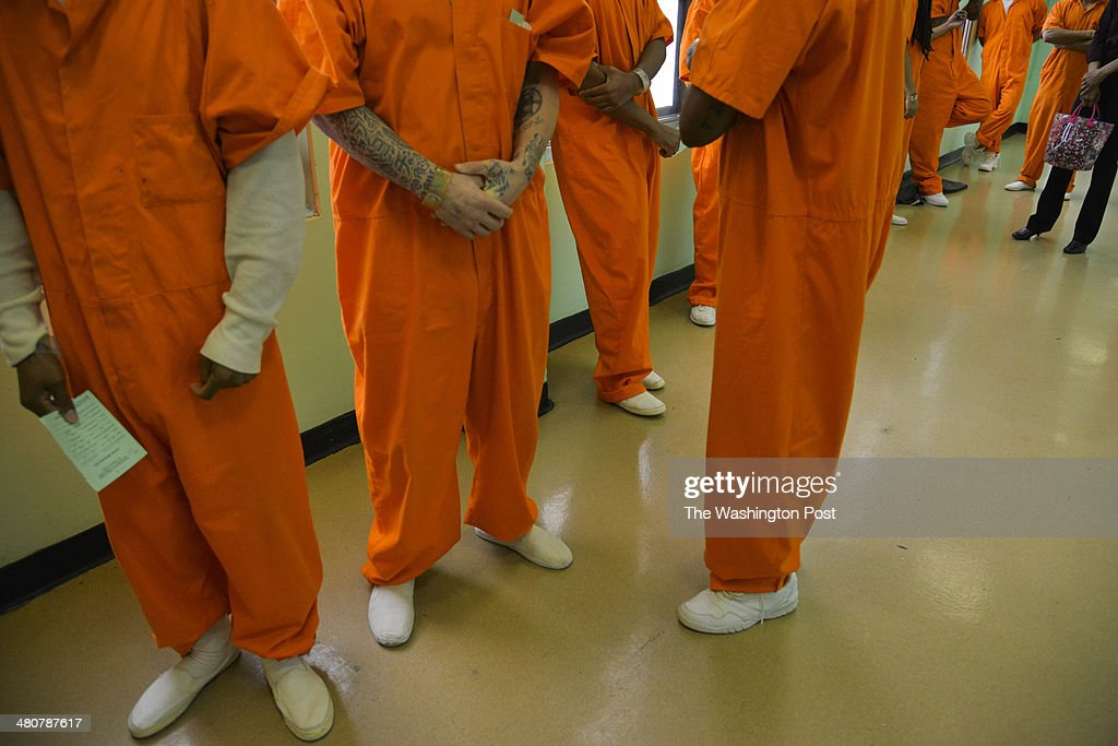 Inmates from the medium and maximum security blocks wait in line to cast their votes at the DC jail as part of early voting in the city's election on...