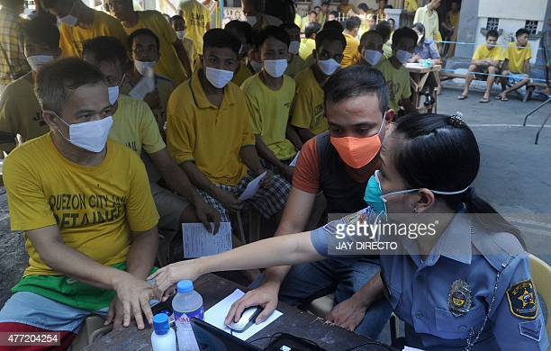 Inmates from the Quezon City jail are processed during a mass screening for Tuberculosis in suburban Manila on June 15 2015 The International...