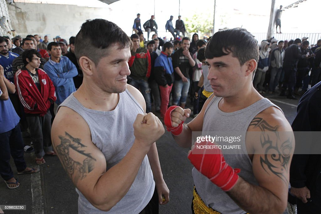 Inmates get ready for a boxing match in Tacumbu prison in Asuncion, Paraguay on Apr. 30, 2016. Tacumbu prison, Paraguay's largest, was built to hold 1,500 inmates but currently houses some 4,000, guarded by 45 poorly-trained guards per shift. Overcrowding, drug dealing, violence, and privileges for a handful of inmates held in so-called VIP cells are part of alarming conditions that undermine human dignity. / AFP / NORBERTO