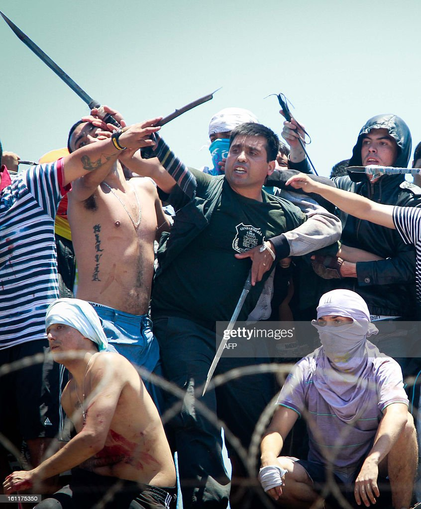 Inmates hold a member of the Chilean Gendarmes during an uprising at a prison in Atnofagasta, Chile on February 9, 2013. Four Gendarmes and ten inmates were injured during the uprising, which was brought under control within a few hours.