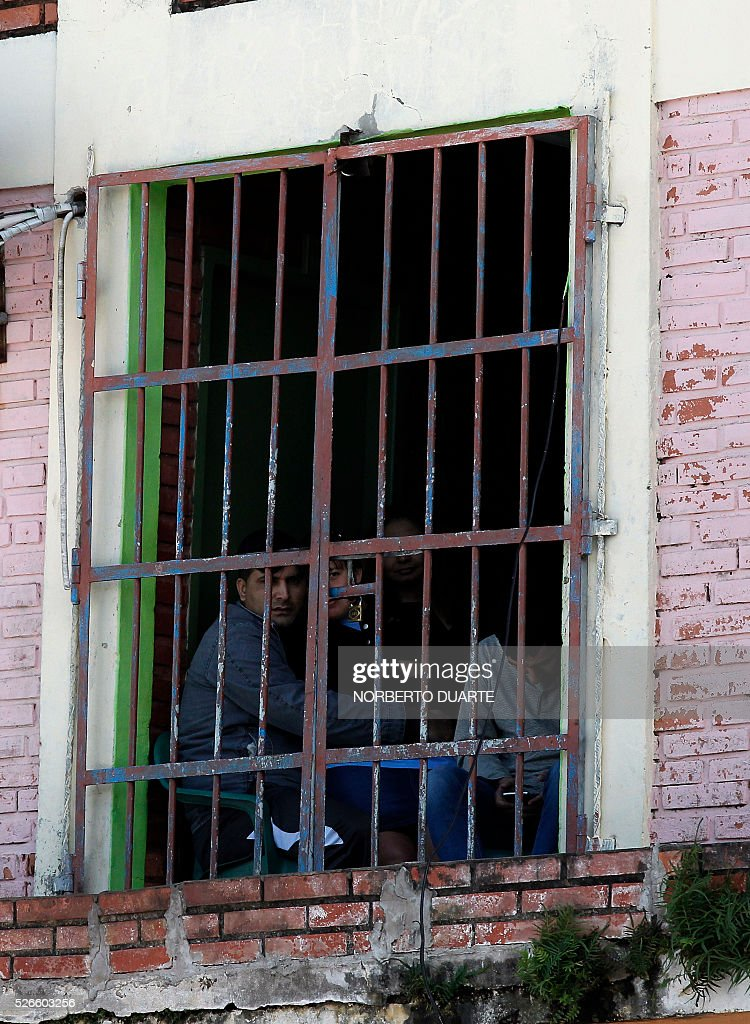 Inmates looking out a window in Tacumbu prison in Asuncion, Paraguay on Apr. 30, 2016. Tacumbu prison, Paraguay's largest, was built to hold 1,500 inmates but currently houses some 4,000, guarded by 45 poorly-trained guards per shift. Overcrowding, drug dealing, violence, and privileges for a handful of inmates held in so-called VIP cells are part of alarming conditions that undermine human dignity. / AFP / NORBERTO
