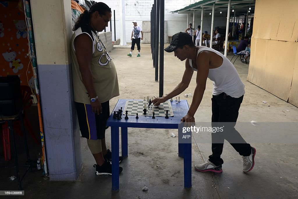 Inmates play chess during the Hugo Chavez First National Penitentiary Games for Freedom inaugurated in the General Penitentiary of San Juan de los Morros , Guarico state, Venezuela on May 23, 2013. AFP PHOTO/Leo RAMIREZ