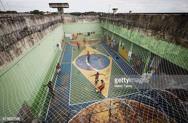 Inmates play soccer on a court painted with the Brazilian flag in the overcrowded Puraquequara prison on February 18 2016 in Manaus Brazil The prison...