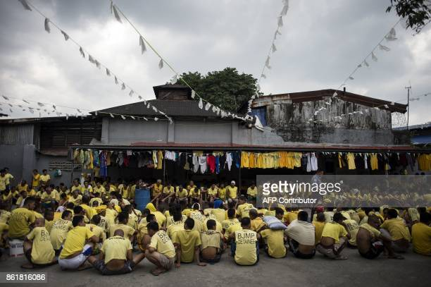 TOPSHOT Inmates sit on the ground as authorities search for contraband at the Manila City Jail on October 16 2017 Contraband such as knives...