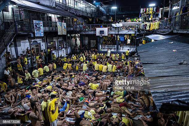 Inmates sleep on the ground of an open basketball court inside the Quezon City jail at night in Manila in this picture taken on July 21 2016 There...