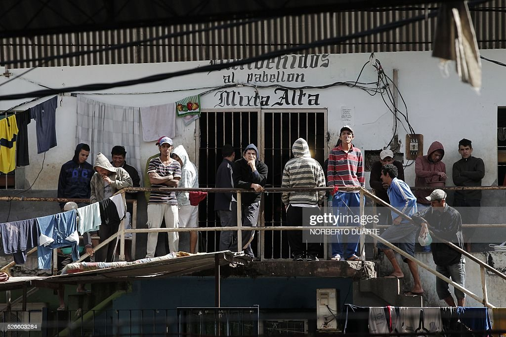 Inmates stand around in Tacumbu prison in Asuncion, Paraguay on Apr. 30, 2016. Tacumbu prison, Paraguay's largest, was built to hold 1,500 inmates but currently houses some 4,000, guarded by 45 poorly-trained guards per shift. Overcrowding, drug dealing, violence, and privileges for a handful of inmates held in so-called VIP cells are part of alarming conditions that undermine human dignity. / AFP / NORBERTO