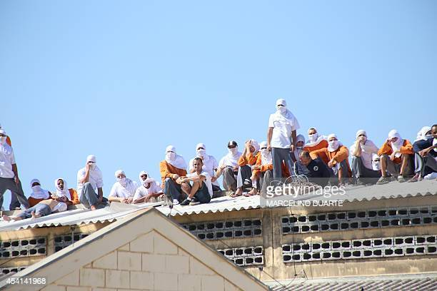 Inmates stand on the roof of the penitentiary in Cascavel Parana state Brazil on August 25 2014 Inmates rioting for better facilities in a Brazilian...