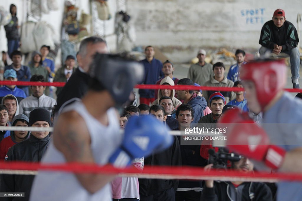 Inmates watch a boxing match in Tacumbu prison in Asuncion, Paraguay on Apr. 30, 2016. Tacumbu prison, Paraguay's largest, was built to hold 1,500 inmates but currently houses some 4,000, guarded by 45 poorly-trained guards per shift. Overcrowding, drug dealing, violence, and privileges for a handful of inmates held in so-called VIP cells are part of alarming conditions that undermine human dignity. / AFP / NORBERTO