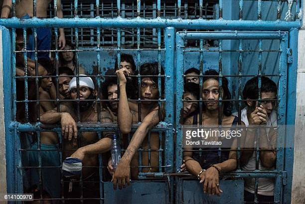 Inmates watch as drug suspects are processed inside a police station on October 12 2016 in Manila Philippines The Duterte administration shifted to...