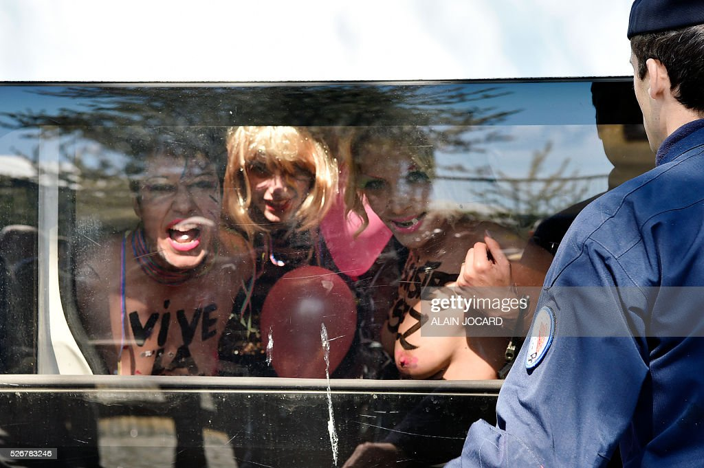 Inna Shevchenko (R) and two other topless Femen activists react inside a police car after protesting outside a banquet held by France's far-right Front National (FN) party in honour of Jeanne d'Arc (Joan of Arc) at the Porte de La Villette in Paris on May 1, 2016. / AFP / ALAIN