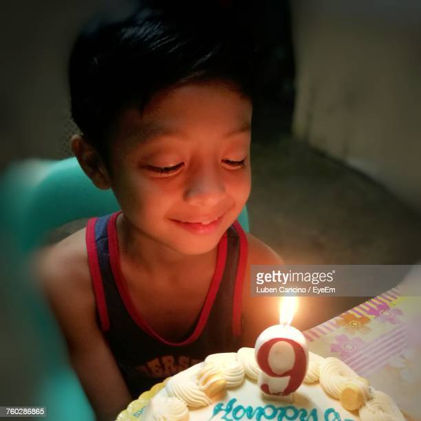 Innocent Boy Looking At Birthday Cake In Room