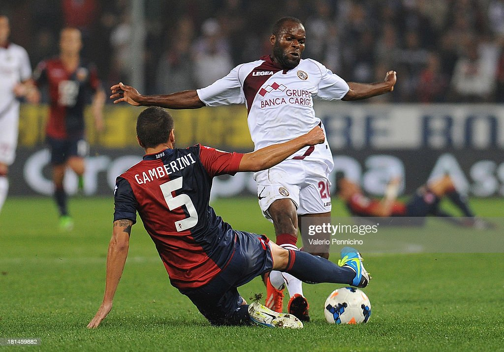 Innocent Emeghara (R) of AS Livorno Calcio is tackled by <a gi-track='captionPersonalityLinkClicked' href=/galleries/search?phrase=Alessandro+Gamberini&family=editorial&specificpeople=695639 ng-click='$event.stopPropagation()'>Alessandro Gamberini</a> of Genoa CFC during the Serie A match between Genoa CFC and AS Livorno Calcio at Stadio Luigi Ferraris on September 21, 2013 in Genoa, Italy.
