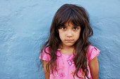 Close up portrait of innocent little girl standing against blue wall, she is looking at camera with serious expression on her face.