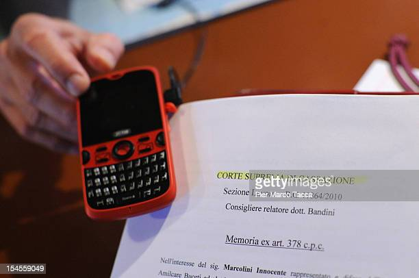 Innocente Marcolini points to his mobile phone in his home on October 19 2012 in Brescia Italy In a landmark workplace compensation case the Supreme...