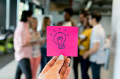 Unrecognizable person holding a sticky note with a lightbulb symbolizing innovation - business concepts