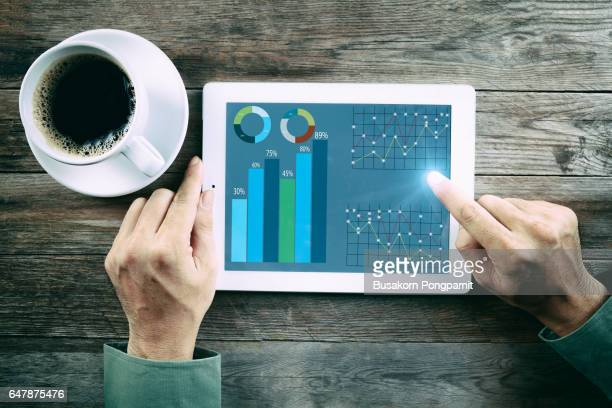 Innovation Start Up Success Growth Concept, hands touch tablet with infographics on the screen, Digital tablet with Finance report charts on screen