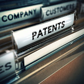 Folder and focus on a tab with the word patents, blur effect. Concept of company innovation.