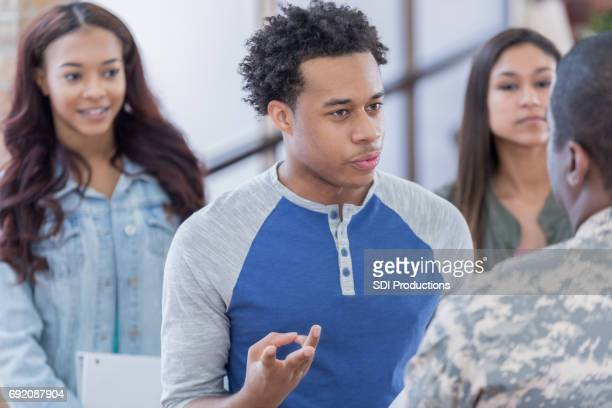 Inquisitive young man asks military recruiter questions at recruitment event