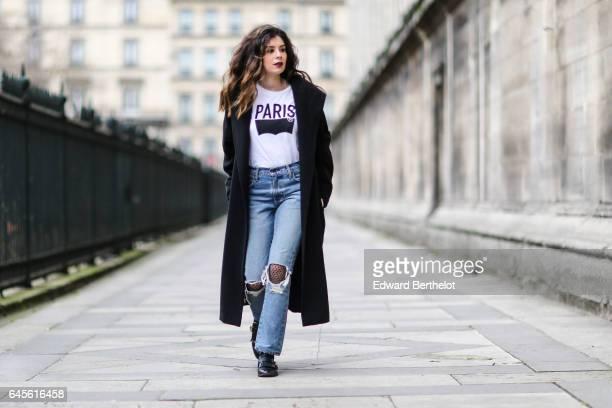 Insaf Bennis fashion blogger from Sparkles in Paris wears a Levi's white tshirt with a 'Paris' logo Levi's blue denim ripped jeans pants Mango black...