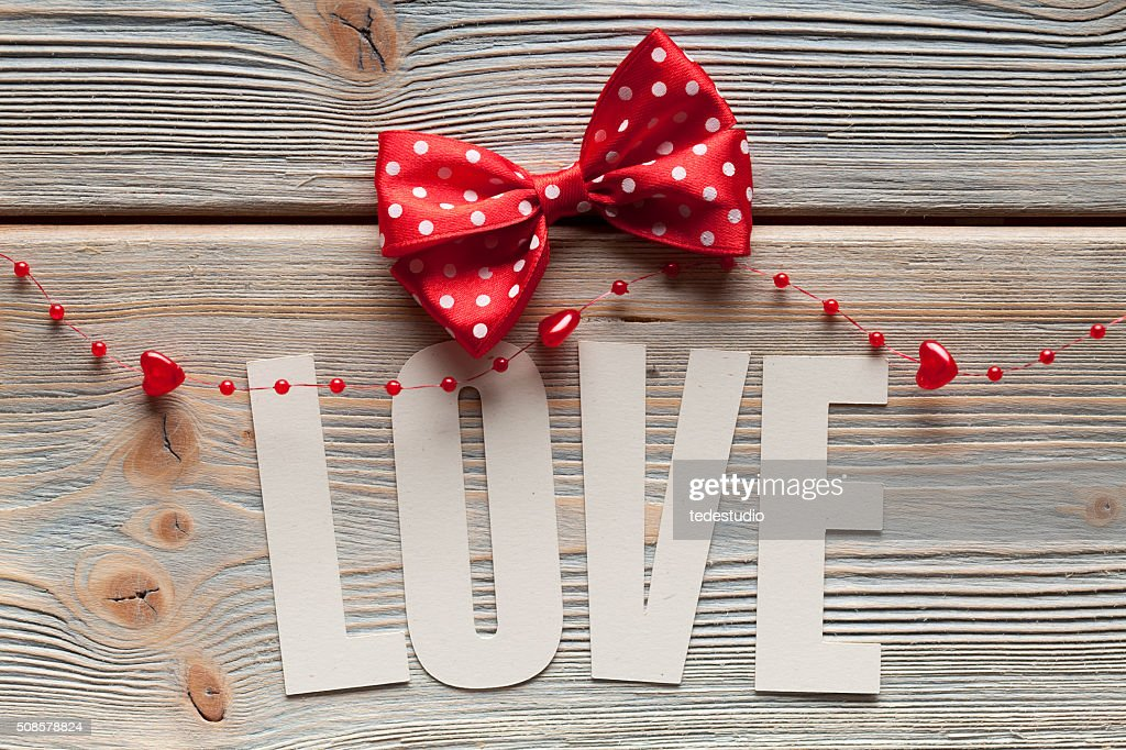 Inscription love and a red bow on wooden background : Stock Photo