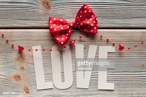 Inscription love and a red bow on wooden background : Stockfoto