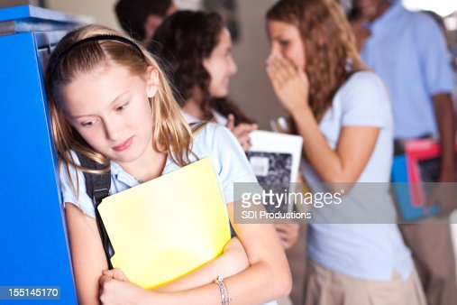 Insecure teenager at school with girls gossiping