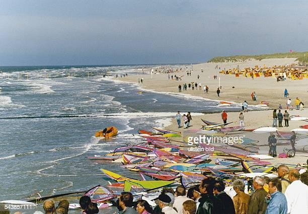 Insel Norderney Ostfriesische Insel BRD Wettbewerb im Windsurfen Zahllose Surbretter liegen am Strand Zuschauer blicken gebannt auf die bewegte...