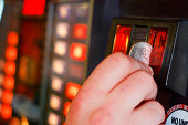 Gambler inserts dollar into slot machine at amusement arcade or casino