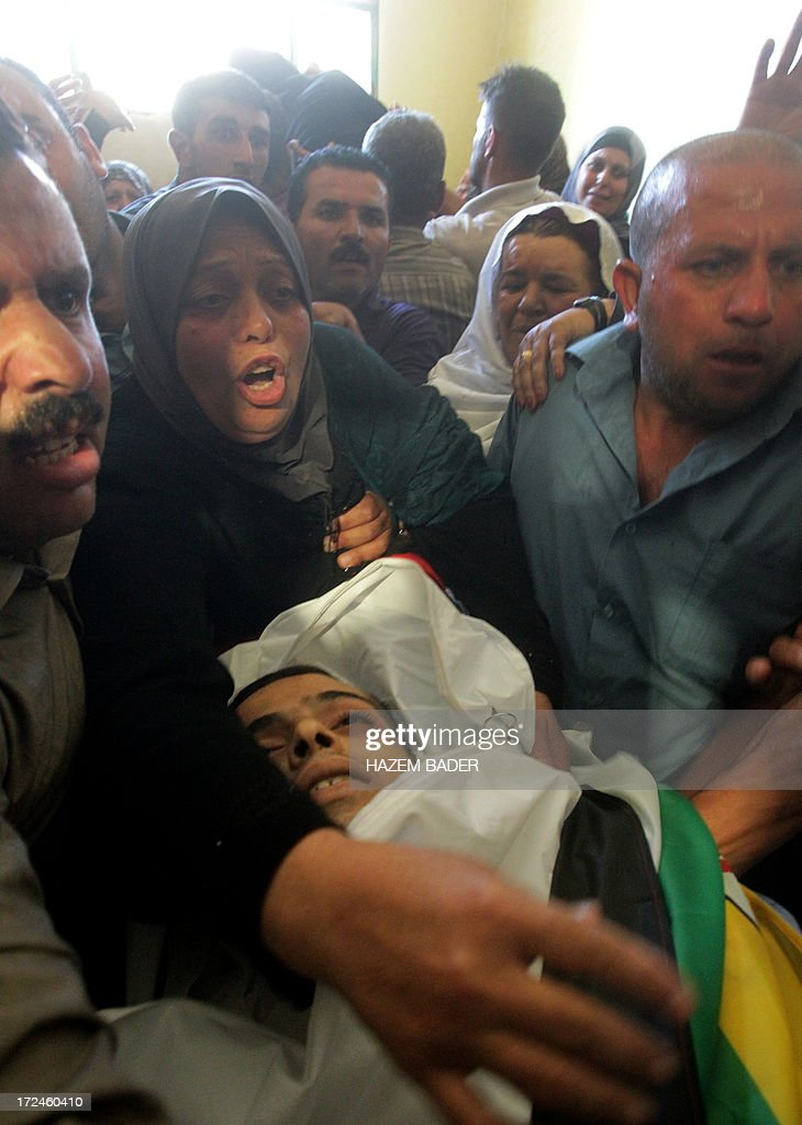 Inshirah, the mother of killed Palestinian youth Moataz Sharawna, 19, bids her son farewell during his funeral in the West Bank village of Dura, on July 2, 2013, after he was knocked down and killed by an Israeli military jeep during overnight clashes in the village. Sharawna died after being hit by the vehicle following several hours of clashes between stone throwers and troops which began at midnight in Dura, which lies just southwest of Hebron, a police spokesman told AFP. AFP PHOTO/HAZEM BADER