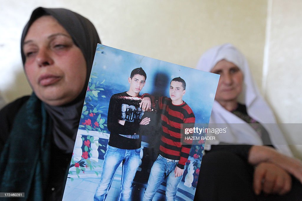 Inshirah, the mother of killed Palestinian youth Moataz Sharawna, 19, holds up his photo (youth in red and black top) prior to his funeral in the West Bank village of Dura, on July 2, 2013, after he was knocked down and killed by an Israeli military jeep during overnight clashes in the village. Sharawna died after being hit by the vehicle following several hours of clashes between stone throwers and troops which began at midnight in Dura, which lies just southwest of Hebron, a police spokesman told AFP. AFP PHOTO/HAZEM BADER