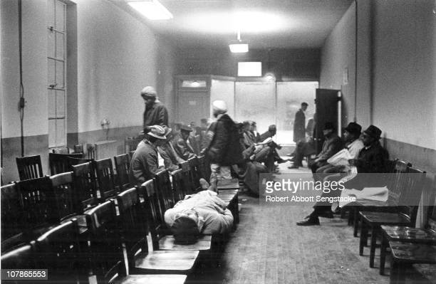 Inside a day labor office a group of African American men sit and talk or sleep on chairs as they wait for work Chicago Illinois 1971