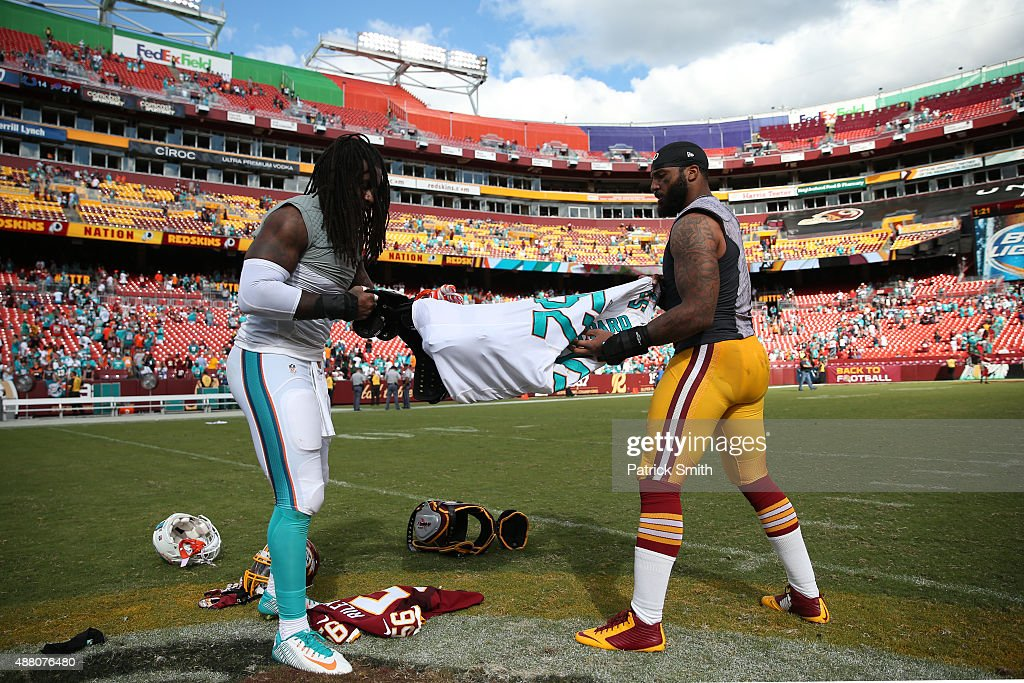 Inside linebacker Perry Riley of the Washington Redskins swaps jerseys with middle linebacker Kelvin Sheppard of the Miami Dolphins after a game at...